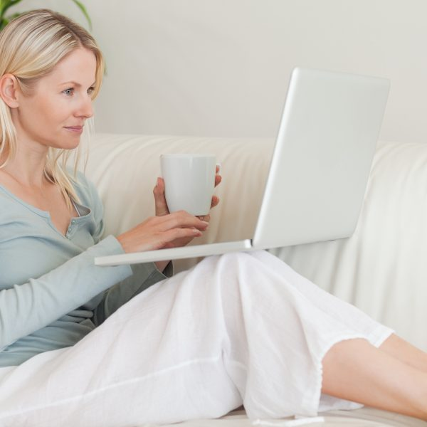 Woman sitting on couch with coffee and laptop